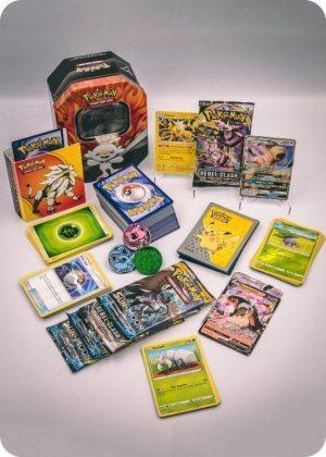 Pokemons mellem pakkeløsning med Pokémonkort, mini mappe og tinbox
